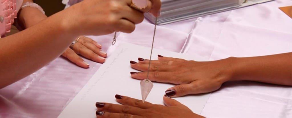 Un pendulo usado para detectar las energías sobre unas manos abiertas